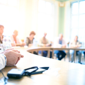 stock-photo-people-at-a-round-table-discuss-different-issues-focus-on-hand-1113593240